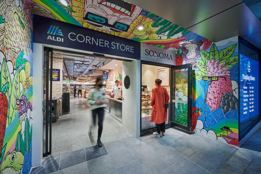 Pour personnaliser chaque Aldi Corner store, l'agence de design Landini Associates a recours à un street artist local (ici Mulga). On aperçoit à droite de l'entrée le kiosque concédé Sonoma proposant boissons chaudes et viennoiseries-pâtisseries à emporter. Photo : Corporate Pixel / Kyle Ford.